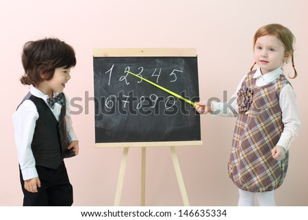 Little girl shows by pointer figures at chalkboard for boy in studio. - stock photo