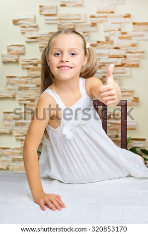Little girl shows ok gesture at light room - stock photo