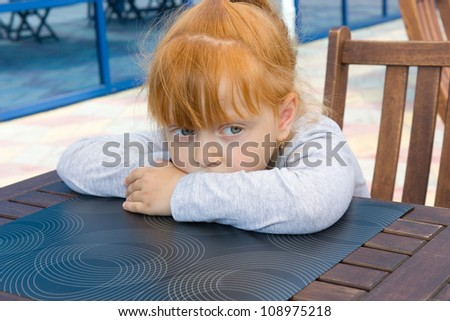 little girl sits at a table - stock photo