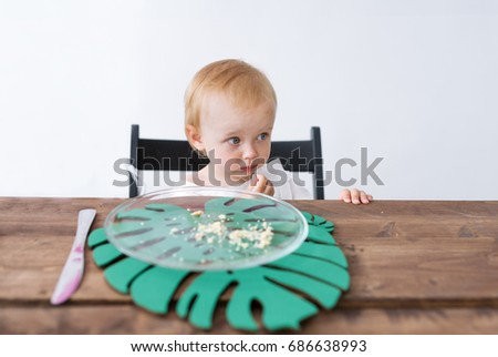 Little girl sits at a table. At the girl her tasty dessert has ended. She is upset.