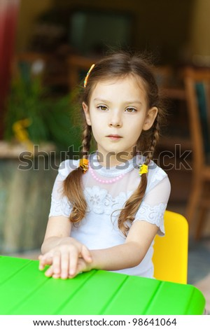 Little girl sits at green children's table and thinking.