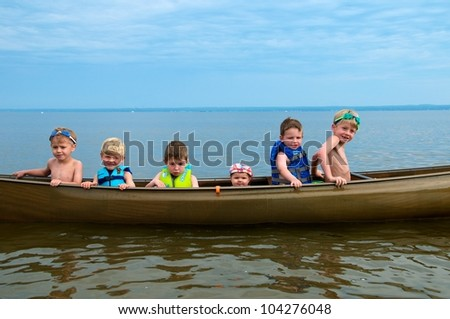 Little girl sits between her five brothers and cousins in a  canoe - stock photo