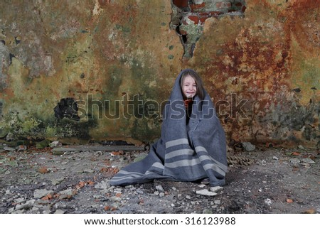 Little girl sits in basement wrapped in blanket and crying with tears on face - loneliness, poverty, despair concept - stock photo