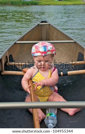 Little girl sits in the canoe holding the paddle getting ready for a ride - stock photo