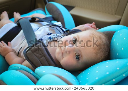 little girl sits in the car seat - stock photo