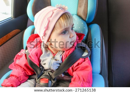 little girl sits in the car seat. The child looks to the side.  - stock photo