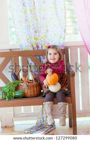 little girl sits on a bench on a terrace with a basket with vegetables