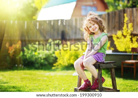 Little girl sits on a chair in the yard of a country house. - stock photo