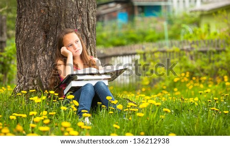 Little girl sits on a grass and dreams while reading a book