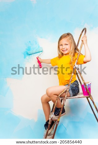 Little girl sits on a metal ladder and holds brush in here hand