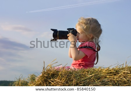 Little girl sits on a pile of hay and sunset photographs - stock photo
