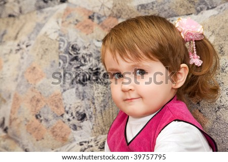 little girl sits on a sofa in a cozy room - stock photo