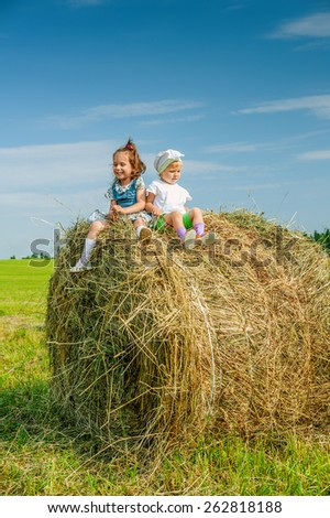 Little girl sits on haystack. - stock photo