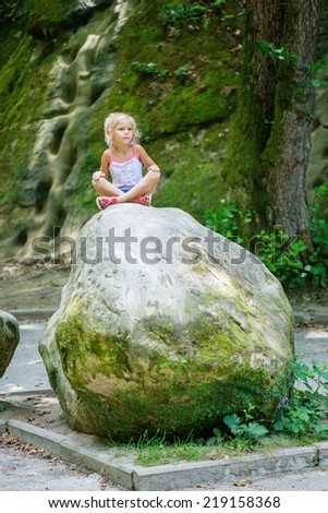 little girl sits on large stone in resort part of city of Goryachiy Klyuch in Krasnodar region of Russia. - stock photo