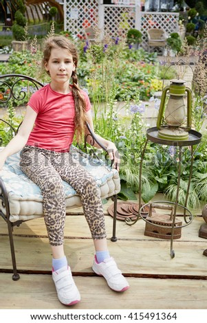 Little girl sits on old-fashioned metal armchair near old lamp against blooming park. - stock photo