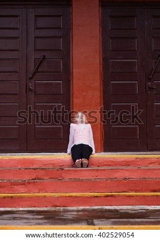 little girl sits on stairs near door  - stock photo