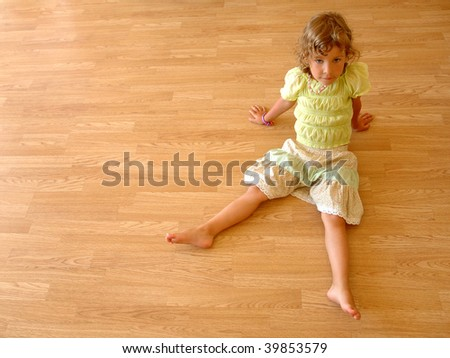 Little girl sits on wooden floor - stock photo