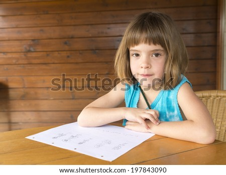 Little girl sitting and drawing on a terrace