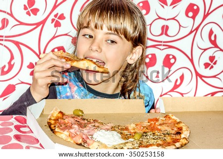 Little girl sitting and eating pizza slice - stock photo