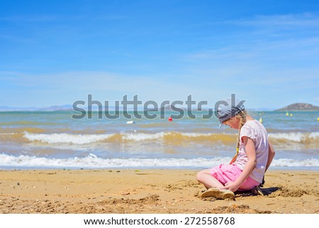 Little girl sitting and playing on the sandy beach - stock photo