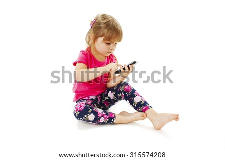 Little girl sitting and sending message on phone mobile. Isolated on white background - stock photo