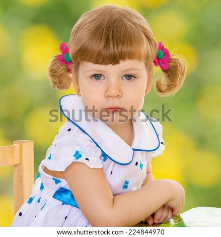 Little girl sitting at a desk and looking into the camera.Happiness, winter holidays, new year, and childhood. - stock photo