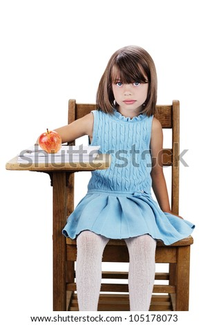 Little girl sitting at a school desk with apple and books. Isolated on a white background with clipping path included.