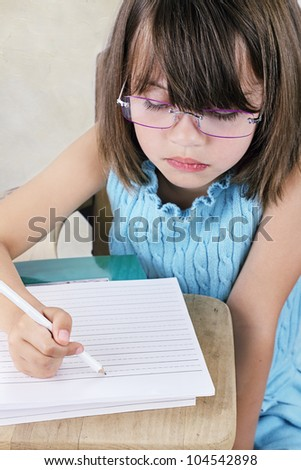 Little girl sitting at a school desk writing. - stock photo