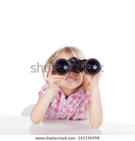 Little girl sitting at a table looking through binoculars viewing something exciting in the distance, on a white background - stock photo