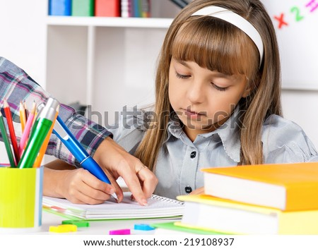 Little girl sitting at desk in the classroom, doing homework at the table.