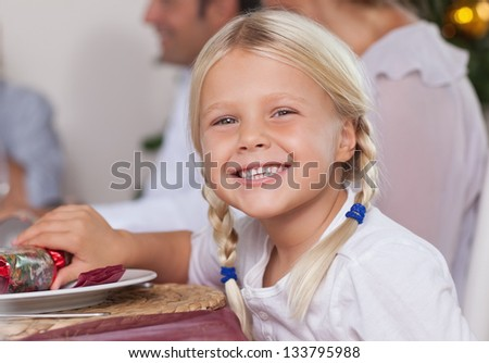 Little girl sitting at dinner table smiling at christmas