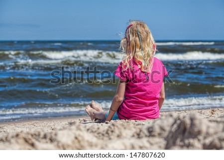 Little girl sitting at seashore watching waves