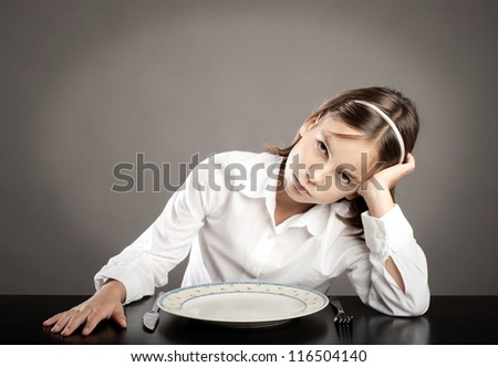 little girl sitting at table in front of an empty dish