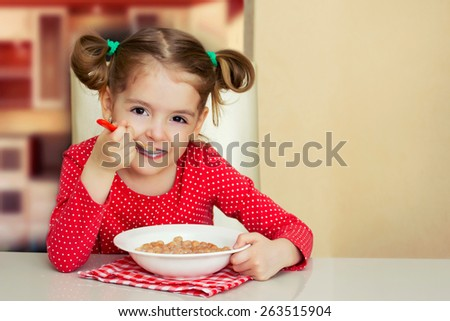 Little girl sitting at the table and eating milk snack. Happy child have a breakfast. Kids nutrition background. - stock photo