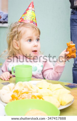 Little girl sitting at the table in her birthday eating cookies - stock photo