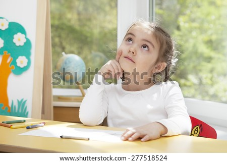 Little girl sitting at the table in thoughts about her next picture  - stock photo