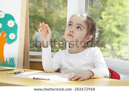 Little girl sitting at the table in thoughts of her next picture