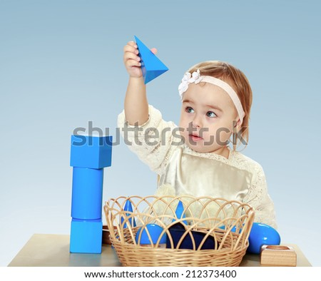 little girl sitting at the table playing with cubes and pyramids on a blue background in the Montessori classroom.the concept of a happy childhood, education of children, teens - stock photo