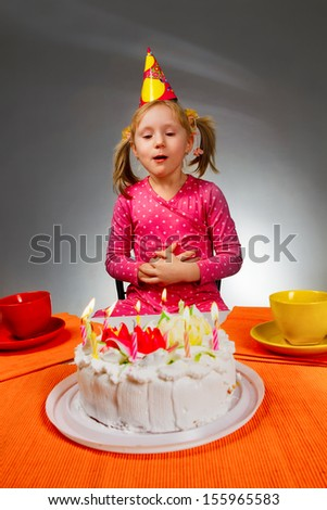 Little girl sitting at the table with cake in her birthday