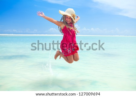 little girl sitting at tropical beach with frangipani flower in her hair - stock photo