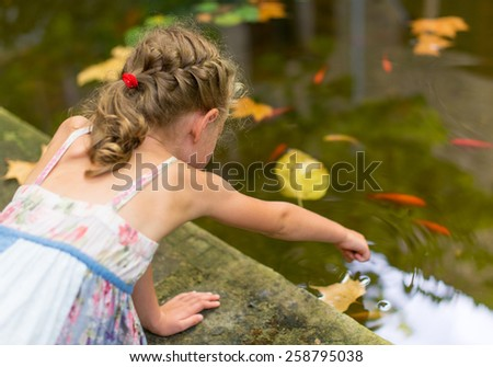 Little girl sitting by the pond with fish. - stock photo