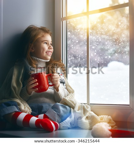 little girl sitting by the window with a cup of hot drink and looking at the winter forest - stock photo