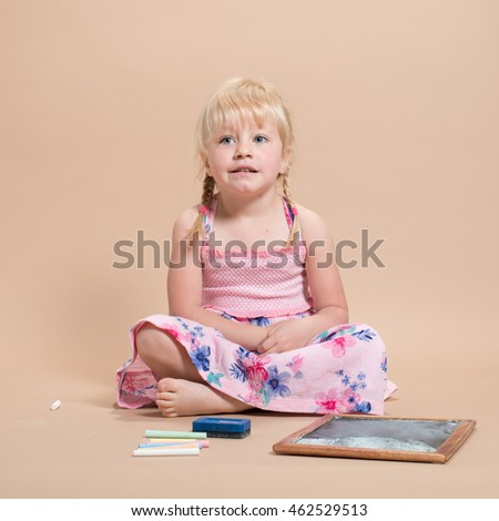 Little girl sitting down ready to play with her chalks