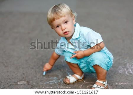 little girl sitting drawing with chalk