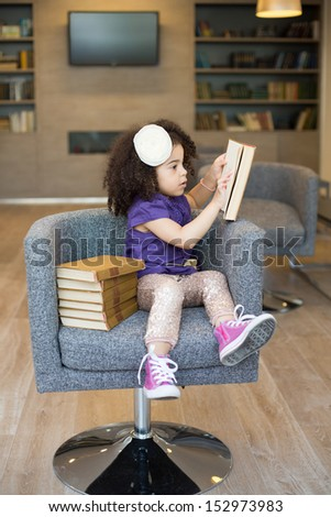Little girl sitting in a chair with a stack of books and reading