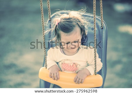little girl sitting in a swing in spring - stock photo