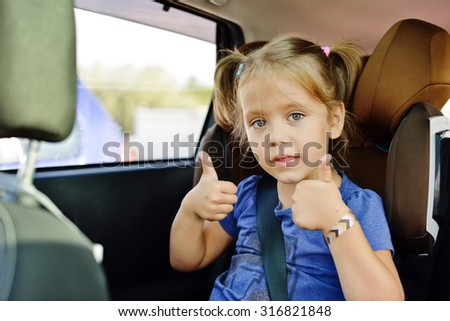little girl sitting in car seat with thumbs up