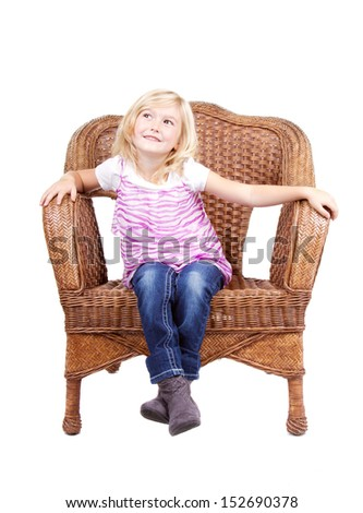 little girl sitting in chair with a happy look on her face, isolated on white background  - stock photo
