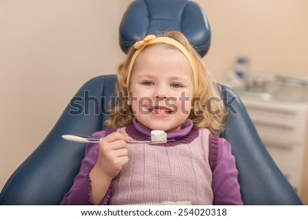 little girl sitting in dentist chair. girl holding toothbrush with tooth paste on foreground - stock photo
