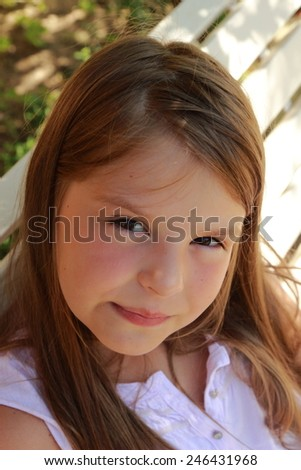 little girl sitting in the summer park bench - stock photo
